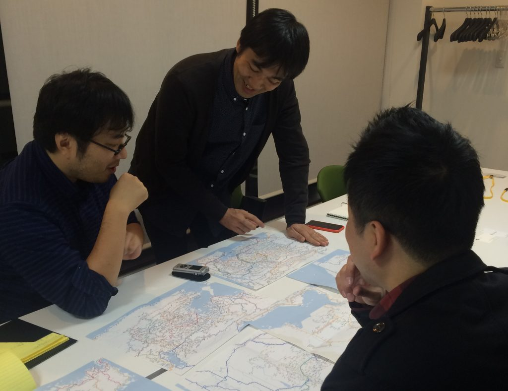 印刷された路線図を食い入るように見つめる(左から)西村さん、井上さん